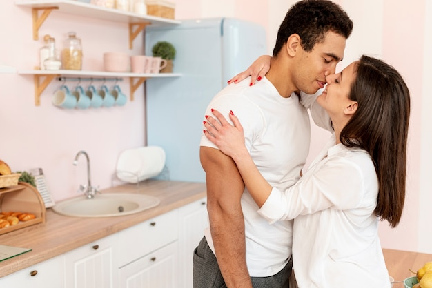 Medium shot couple kissing in the kitchen
