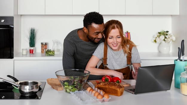 ノートパソコンを見ているミディアムショットのカップル