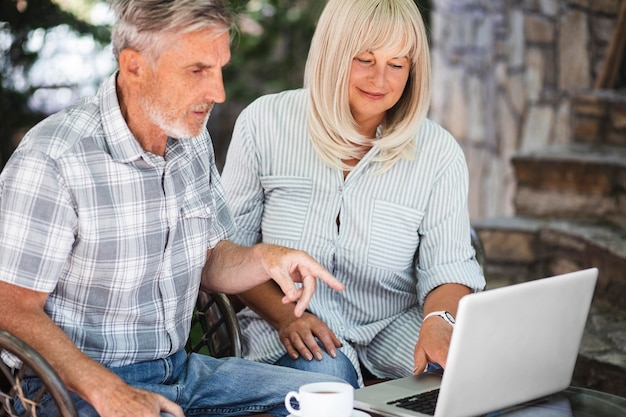 Medium shot couple looking at laptop