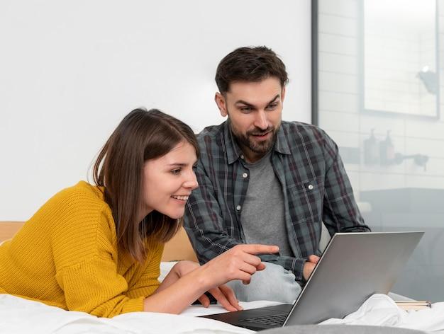Medium shot couple looking at laptop