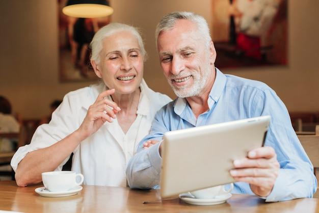 Medium shot couple looking at a tablet