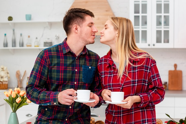 Medium shot couple ready to kiss in the kitchen