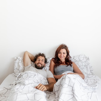 Medium shot of couple relaxing in bed