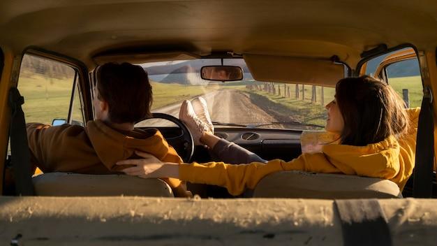 Coppia di tiro medio seduto in macchina