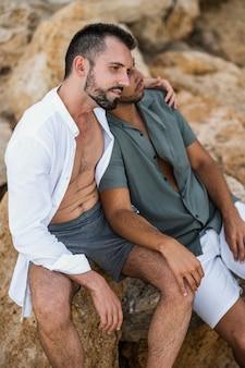 岩の上に座っているミディアムショットのカップル