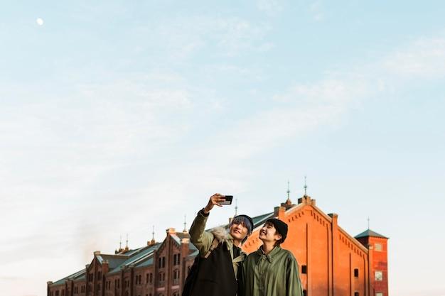 屋外で自分撮りをするミディアムショットのカップル