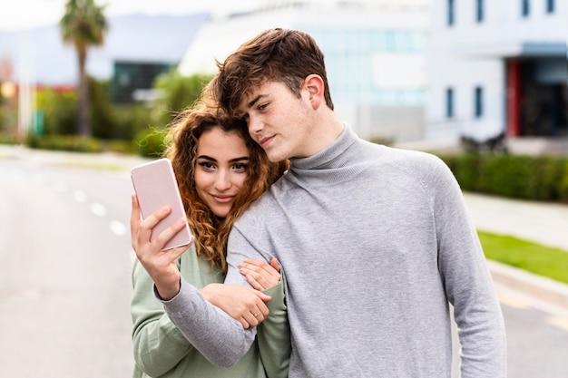 Coppie del colpo medio che prendono selfie all'aperto