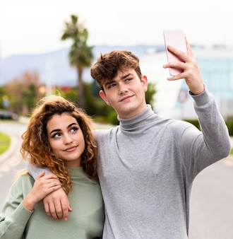 Medium shot couple taking selfie together