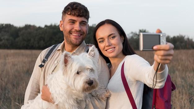 Coppie del colpo medio che prendono selfie con il cane