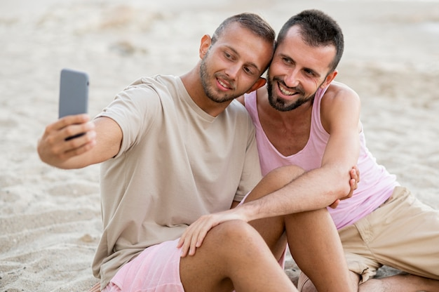 Medium shot couple taking selfies on beach
