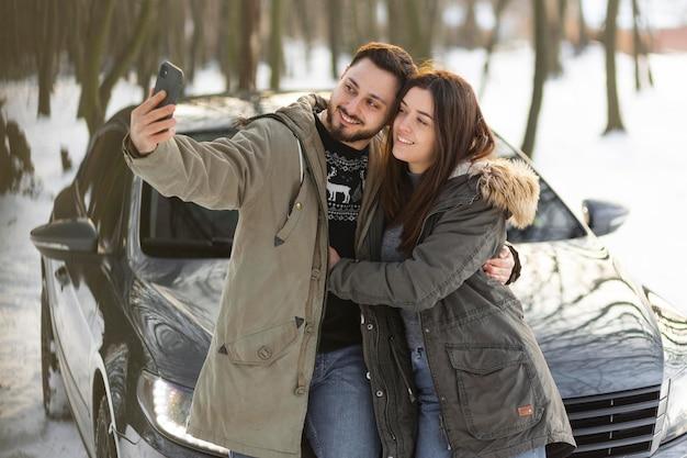 Medium shot couple taking selfies