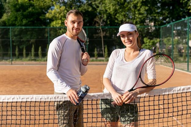 Medium shot couple on tennis court