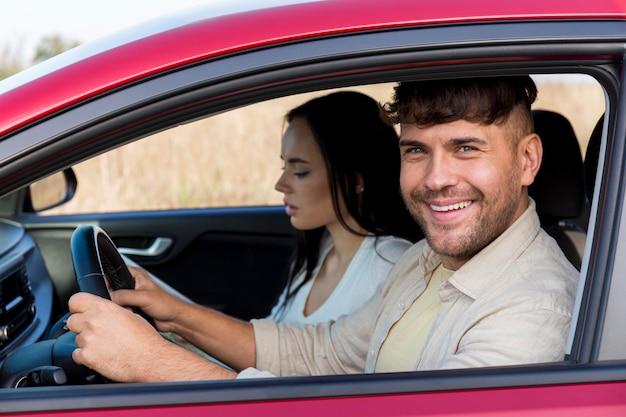 Пара среднего кадра, путешествующая на машине