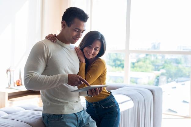 Medium shot of couple using tablet
