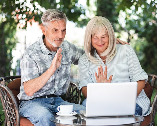 Medium shot couple waving at laptop