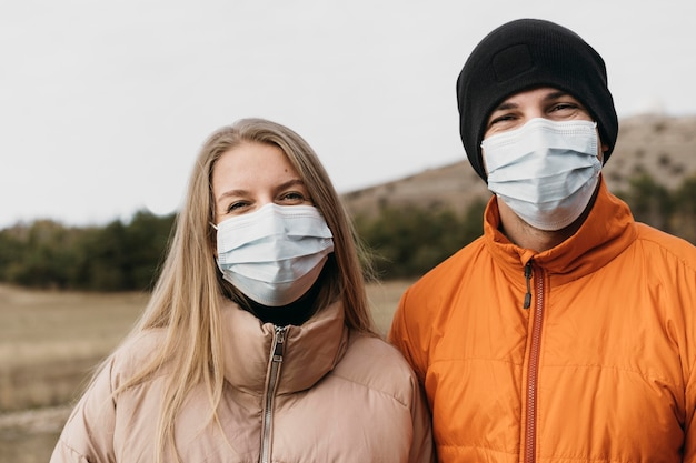 Medium shot couple wearing medical masks