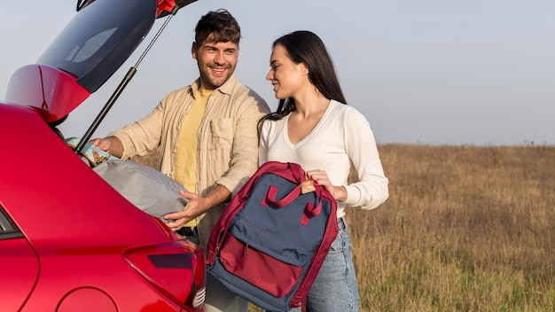 Medium shot couple with backpacks outdoors