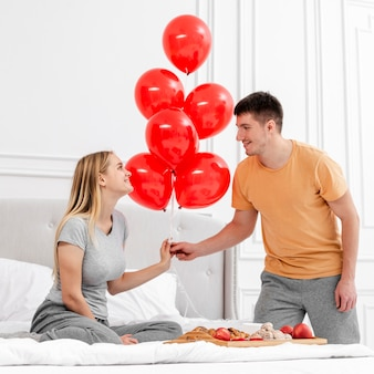 Medium shot couple with balloons in bedroom
