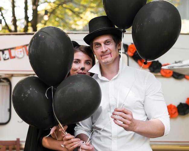 黒い風船のミディアムショットのカップル