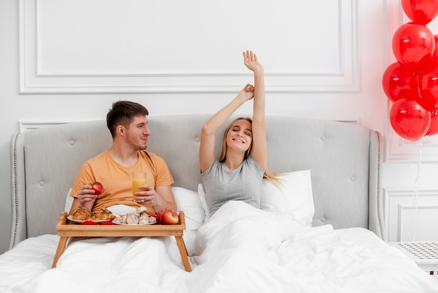 Medium shot couple with breakfast and balloons in bedroom