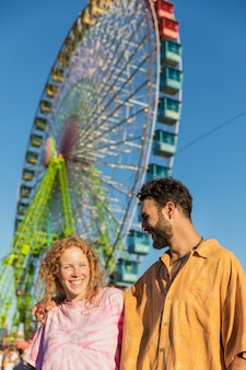 Medium shot couple with carnival wheel