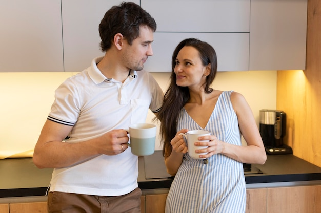 コーヒーカップとミディアムショットのカップル
