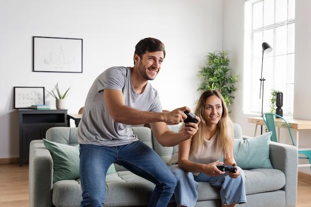 屋内のコントローラーとミディアムショットのカップル Premium写真