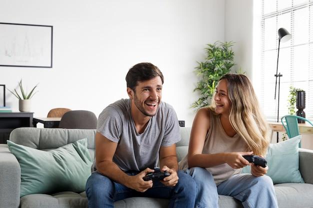 コントローラーが遊んでいるミディアムショットのカップル Premium写真