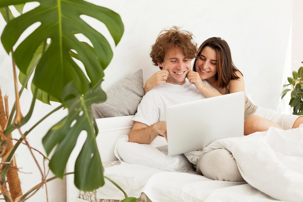 Medium shot couple with laptop in bedroom