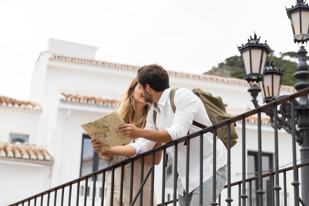 Medium shot couple with map kissing