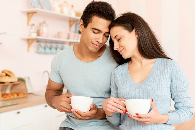 Medium shot couple with mugs in the kitchen