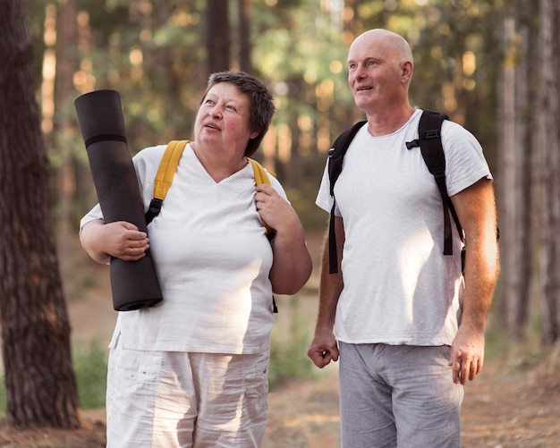 Medium shot couple with yoga mat