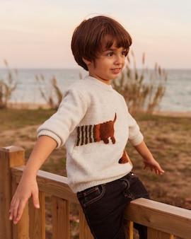 Средний снимок милый мальчик на заборе
