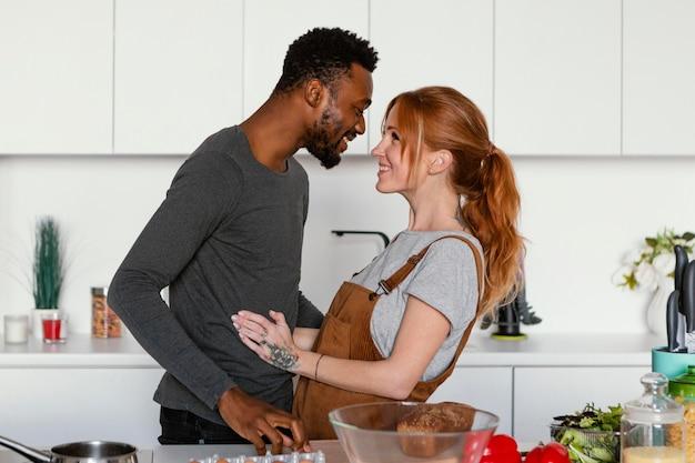 キッチンでミディアムショットのかわいいカップル
