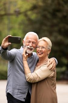 ミディアムショットのかわいいカップルが自分撮りを撮る