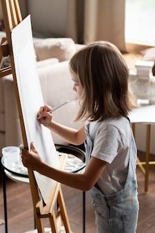 Средний снимок милая девушка рисует дома