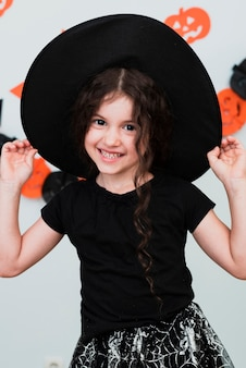 Medium shot of cute little girl with witch hat