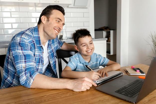 Medium shot dad and boy with laptop
