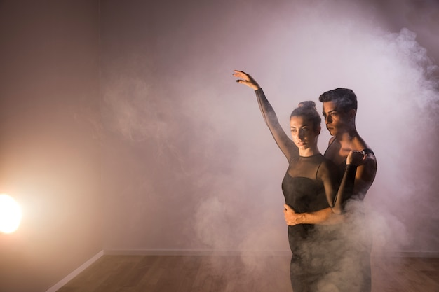 Medium shot dancers couple in smoke