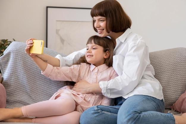 ミディアムショットの娘と母親が自分撮りをしている