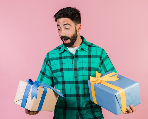 Medium shot delighted guy holding gifts