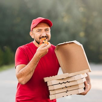 Medium shot delivery guy eating pizza