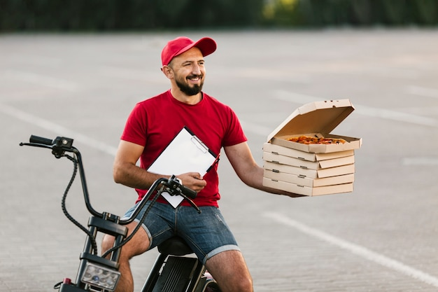 Medium shot delivery guy holding up boxes with pizza