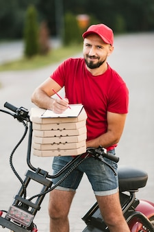 Medium shot delivery guy with motorcycle and pizza