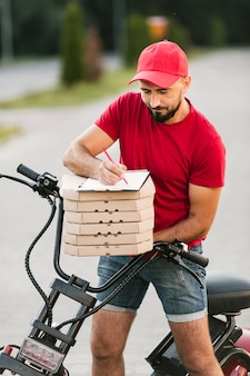 Medium shot delivery guy writing in clipboard