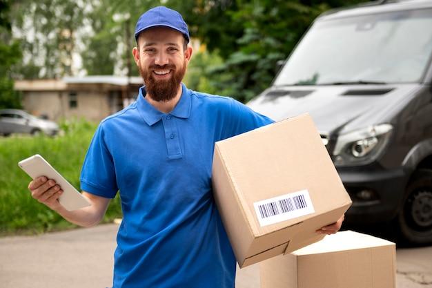 Medium shot delivery man carrying box