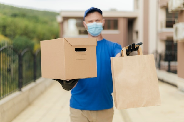Medium shot delivery man holding box and bag