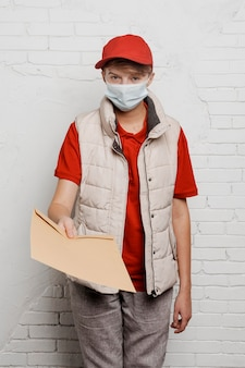 Medium shot delivery man holding envelope