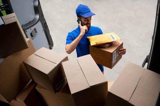 Medium shot delivery man talking on phone Free Photo
