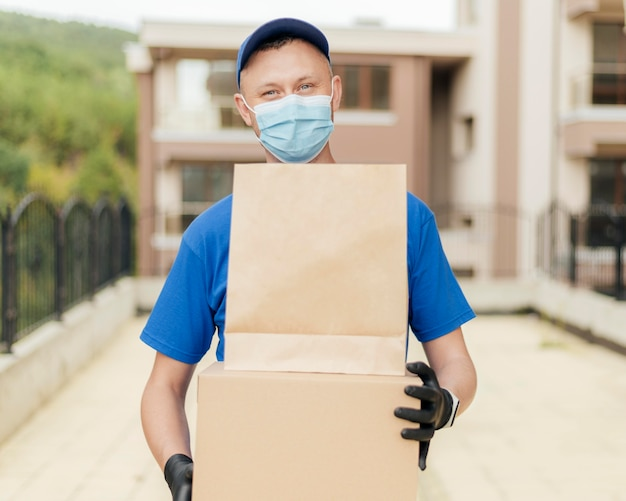 Medium shot delivery man wearing mask